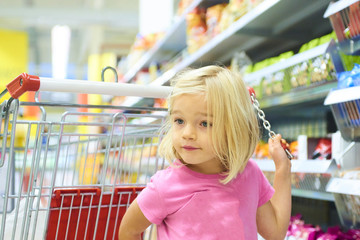 Little Child Blond Girl Shopping in the supermarket, pushing trolley, looking for sweets