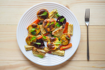 Baked vegetables in large pieces on a plate. Vegetarian diet. Close up. Vegetable garnish grill.