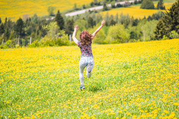 Back of young woman running, jumping in air and smiling on countryside yellow dandelion flower fields in summer grass in Ile D'Orleans, Quebec, Canada back