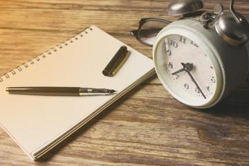 Blank notebook with vintage alarm clock
