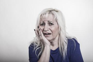Mittfünfzigerin mit Zahnschmerzen fasst sich an die Fange und macht einen tragischen Gesichtsausdruck