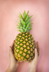 Female hand with pineapple at pink background