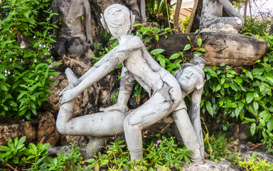 Old stone statue depicting a Nuad Boran (Thai massage) move at famous Wat Pho (Buddhist Temple) in Bangkok, Thailand
