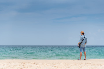 Young Asian man photographer standing on the beach. sea and sky horizon in background. Travel holiday or vacation in summer season concept