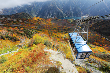 Aerial scenery of a scenic cable car flying over the beautiful autumn valley in the Tateyama Kurobe Alpine Route, Japan ~ Breathtaking view from Daikanbo over magnificent colorful autumn valley