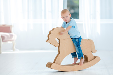 Cute, smiling, white, two years old boy in blue t-shirt and jeans rocking on wooden handmade horse. Little child having fun with pony toy. Concept of early childhood education, happy family
