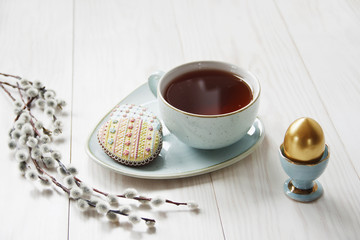 Close-up photo of Easter golden egg on wooden background with willows branches and cup of tea on plate with cookies