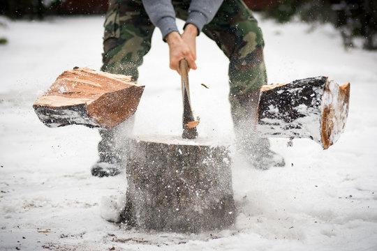 lumberjack cutting wood in snow