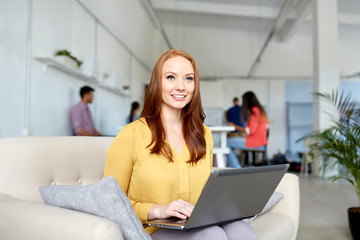 business, education, technology and people concept - happy young woman with laptop computer working at office