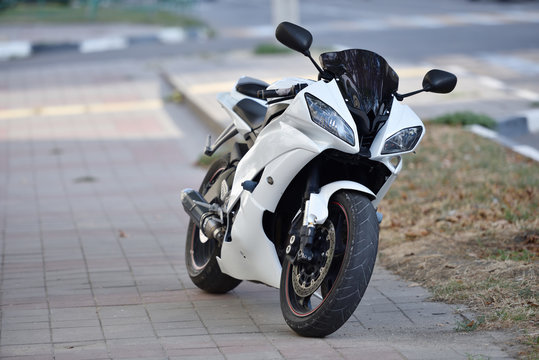 A parked sports bike is standing on the sidewalk in the city. The sports motorcycle is black and white