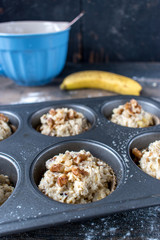 mixing ingredients from scratch for banana nut muffins in muffin tins top view