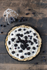 not perfect homemade pie with whipped cream filling and fresh summer blackberries and blueberries top view