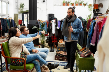 sale, shopping, fashion and people concept - friends choosing clothes at vintage clothing store and showing like or dislike