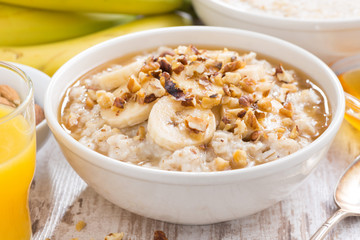 healthy breakfast - oatmeal with banana, honey and walnuts in a bowl