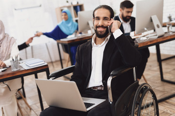 Disabled arab man in wheelchair working in office. Man is working on laptop.