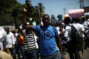 A photographer walks rising his camera to protest during a march to demand information about a missing local, freelance photojournalist Vladjimir Legagneur, in Port-au-Prince