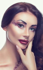 Portrait of a beautiful young brunette girl, which was applied make-up in a beauty salon.
