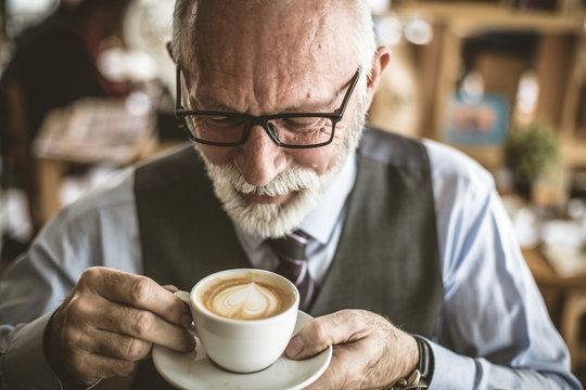 Close up image of senior businessman drinking coffee.