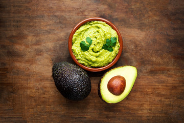 Avocado with guacamole sauce on a dark wood background. Half and whole avocadoes close up. Top view. Copy space.