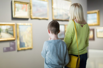 Ordinary mother and son exploring paintings
