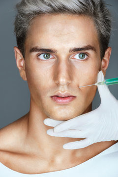 Beautiful Man getting Botox injection in the nasolabial folds. Professional cosmetician making rejuvenate injection. Beauty concept