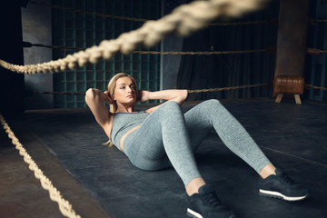 Self determined sporty girl with blonde hair lying on floor inside boxing ring, keeping hands behind her head while doing sit ups, wearing black sneakers and gray sports outfit. Selective focus