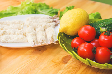 Raw shrimp in batter ready for roasting next to a basket of cucumber lemon cucumbers and tomatoes against the background of lettuce leaves on a wooden table