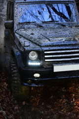 Dirty offroad car, close up. SUV covered with mud