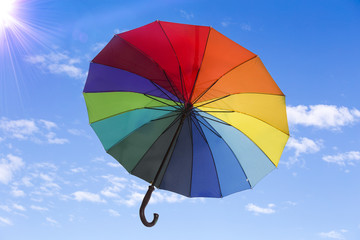 Rainbow umbrella against the sky