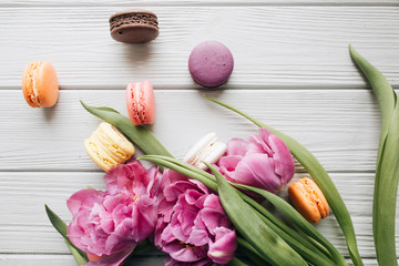 Delicious colorful macaroons and pink tulips on white wooden table, sweet dessert