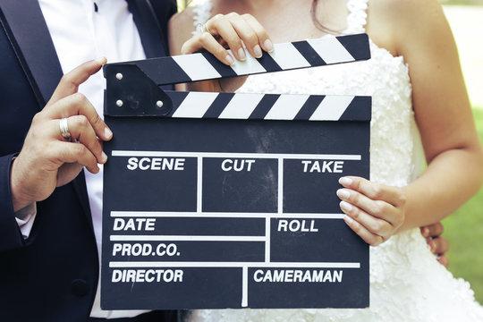 Happy beautiful bride and groom, woman holds clapper board, cinema board