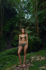 Slender girl in a green swimsuit in a thick jungle, tropical beauty.