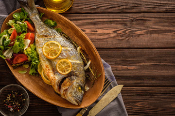 Grilled Dorado with lemon, thyme, rosemary and fresh salad on the wooden table.