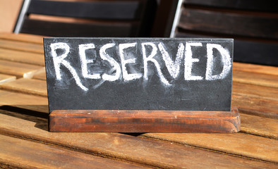Reserved table. The reserved logo. Booking badge. Wooden reservation sign. Reserved table in the restaurant. Hungry. Busy.