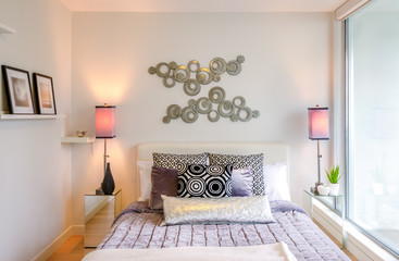 Modern bright bedroom interior with designer pillows in a luxury house.