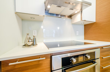 Modern, bright, clean, kitchen interior with stainless steel appliances and wooden cabinets in a luxury house.