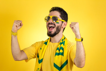 Brazilian supporter of National football team is celebrating, cheering. Male fan.