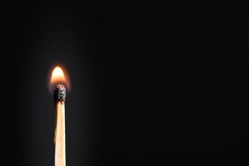 Match with a very weak, discontinuous flames on a black background closeup