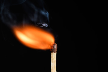 Match with flame blows off to the side on a black background closeup