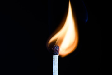 Match with flames in the shape of the upper side of the bulb on a black background closeup