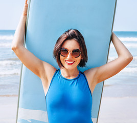 Surfer girl in big sunglasses with long board posing on the ocean beach