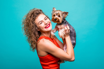 Beautiful woman's in red dresss with Yorkshire terrier dog gives kisses isolated on color background