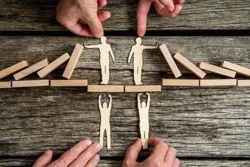 Business teamwork and cooperation concept with the hands of four businesspeople supporting paper cut outs