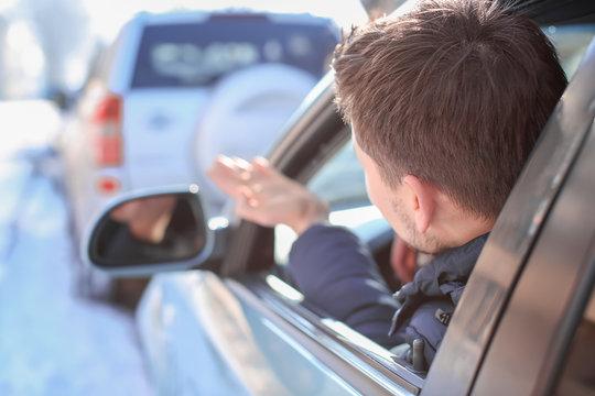 Emotional young man inside car in traffic jam