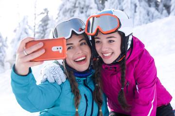 Young women taking selfie at ski mountain resort. Winter vacation