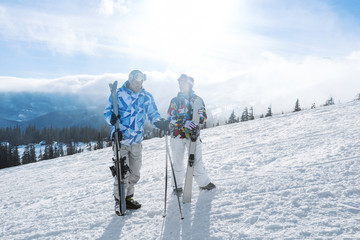 Couple on ski piste at snowy resort. Winter vacation