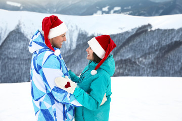 Happy couple in warm mittens and Santa hats at snowy resort. Winter vacation