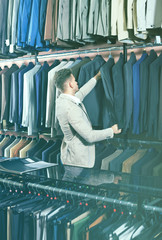Young man choosing new suit in men's cloths store