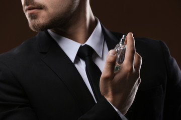 Handsome man in suit using perfume on dark background, closeup