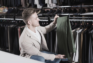 Ordinary man choosing new trousers